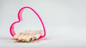 Färben Sie die Bleistifte, die in rotes Herzsymbol legen und stellen Sie Liebe zur Kreativitätszeichnung dar Lizenzfreie Stockfotografie