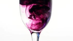 Färben Sie die Tinte, die in Glas Wasser auf weißem Hintergrund fließt stock video