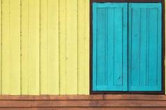 Färben Sie gelbe blaue orange hölzerne Wand und Fenster Lizenzfreie Stockfotografie