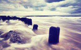 Färben Sie getontes Bild eines leeren Strandes mit unscharfem Wasser Stockfoto