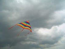 Färben Sie hellen Flugwesendrachen gegen den Sturmhimmel Lizenzfreies Stockbild