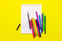 Färben Sie Markierungen und ein Notizbuch auf einem gelben Hintergrund Stockfoto
