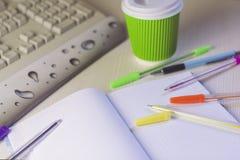 Färben Sie Stifte und Notizbuch mit Kaffee und Tastatur Stockfotografie
