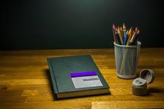 Färben Sie ZeichenstiftBleistiftspitzer und Sketchbook für Kunststudenten auf dem Tisch Lizenzfreie Stockfotos
