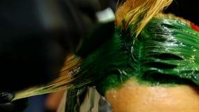 Färbendes Haar des Berufsfriseurs Mehrfarben mit dem Ausdehnen des Farbtons Leuchtstoffbeflecken stock video footage