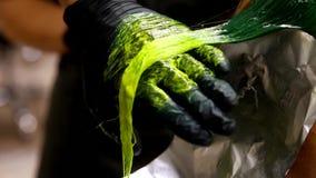 Färbendes Haar des Berufsfriseurs Mehrfarben mit dem Ausdehnen des Farbtons Leuchtstoffbeflecken stock video