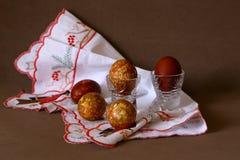 Färbte eine Zwiebelschale des Eies in den Kristallgläsern bis zum einem hellen Feiertag von Ostern auf der gestickten weißen Serv stockfotos