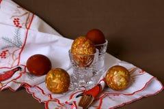 Färbte eine Zwiebelschale des Eies in den Kristallgläsern bis zum einem hellen Feiertag von Ostern auf der gestickten weißen Serv lizenzfreie stockfotografie