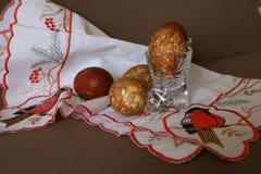 Färbte eine Zwiebelschale des Eies in den Kristallgläsern bis zum einem hellen Feiertag von Ostern auf der gestickten weißen Serv stockbild