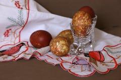Färbte eine Zwiebelschale des Eies in den Kristallgläsern bis zum einem hellen Feiertag von Ostern auf der gestickten weißen Serv lizenzfreie stockfotos