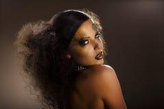 Färbung. Das stilisierte Gesicht der Frau mit goldenem Make-up. Kreative moderne Körper-Kunst stockfotografie