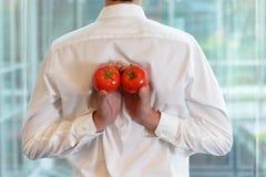 Färdig affärsman med tomater som ett healhy mellanmål Arkivfoton