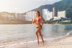 Färdig bärande bikinispring för kvinnlig idrottsman nen på stranden med solen som in camera skiner, och hotellsemesterortkullar i royaltyfri foto