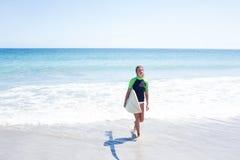 Färdig blond kvinna som går i vatten- och innehavsurfingbrädan Arkivbild