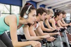 Färdig grupp människor som tillsammans använder motionscykelen arkivbild