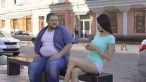 Färdig härlig kvinna som ignorerar fett mansammanträde på bänken, ledsen unconfident ungkarl lager videofilmer
