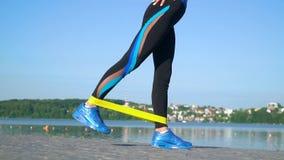 Färdig idrotts- kvinna i sportswear genom att använda den elastiska musikbandet med elasticitetsben och all kropp nära sjön Göra  arkivfilmer