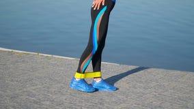 Färdig idrotts- kvinna i sportswear genom att använda den elastiska musikbandet med elasticitetsben och all kropp nära sjön Göra  stock video