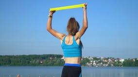 Färdig idrotts- kvinna i sportswear genom att använda den elastiska musikbandet med elasticitetshänder och all kropp nära sjön Gö arkivfilmer