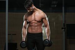 Färdig idrottsman nenDoing Exercise For biceps Arkivfoton