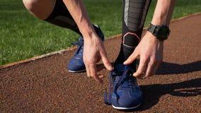 Färdig jogger som binder båda skosnöre, innan att köra övning på spår lager videofilmer