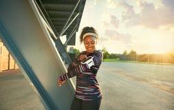 Färdig kvinna för afrikansk amerikan som väljer musik från en app för att köra på solnedgången royaltyfria bilder