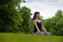 Färdig kvinna för härligt barn som mediterar, andas som sitter med korsade ben i Lotus Posture i parkera på sommardag Royaltyfri Bild