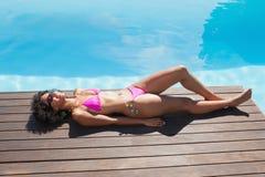 Färdig kvinna i liggande poolside för rosa bikini royaltyfri foto