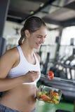 Färdig kvinna som äter sund sallad efter genomkörare royaltyfria foton