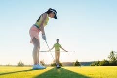 Färdig kvinna som övar slå teknik under golfgrupp med Royaltyfri Fotografi