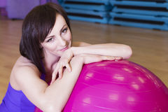 Färdig kvinna som gör övningar med en boll på ett mattt i en idrottshall Royaltyfria Bilder