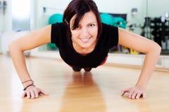 Färdig kvinna som gör press-UPS på idrottshallen Royaltyfria Foton