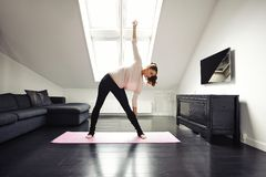 Färdig kvinna som gör sträcka övning hemma Arkivbild