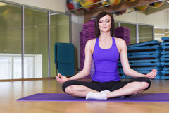 Färdig kvinna som gör yogaövning på ett mattt i en idrottshall Arkivbild