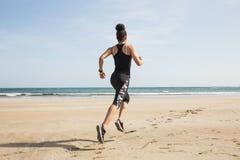 Färdig kvinna som joggar på sanden arkivbilder