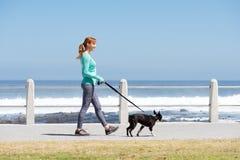 Färdig kvinna som ler och går hunden på banan vid havet Royaltyfri Foto