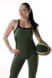 Färdig kvinna som rymmer en idrottshallboll vid hennes sida Arkivfoton