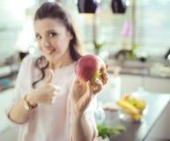 Färdig kvinna som rymmer ett nytt äpple royaltyfri fotografi