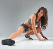 Färdig kvinna som sträcker hennes ben för att värma din kropp upp Arkivfoton