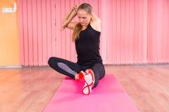 Färdig kvinna som sträcker kroppen, medan sitta på mattt Royaltyfri Foto