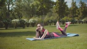 Färdig kvinna som talar på telefonen som ligger på matt det fria arkivfilmer