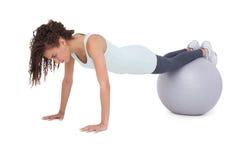 Färdig kvinna som utarbetar på övningsboll Royaltyfri Foto
