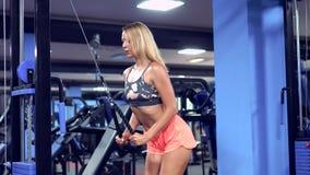 Färdig kvinnagenomköraretriceps som lyfter vikter i idrottshall arkivfilmer
