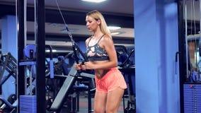 Färdig kvinnagenomköraretriceps som lyfter vikter i idrottshall stock video