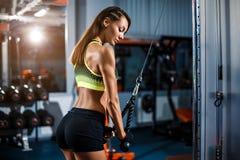 Färdig kvinnagenomköraretriceps som lyfter vikter i idrottshall Arkivfoto