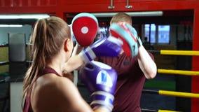 Färdig kvinnlig boxareutbildning med boxninglagledaren på idrottshallen Wellness sund livsstil, strid, motivation, cardio genomkö stock video
