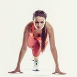 Färdig kvinnlig idrottsman nen som är klar till överkörd grå bakgrund Kvinnlig konditionmodell som förbereder sig för en sprinta Royaltyfri Foto