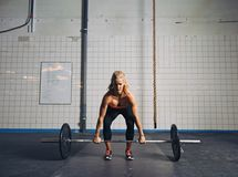 Färdig kvinnlig idrottsman nen som utför en deadlift fotografering för bildbyråer