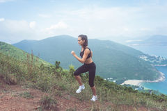Färdig kvinnlig jogger som övar, kör som är stigande med havet, och berg i bakgrund Royaltyfri Fotografi