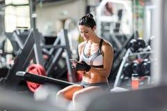 Färdig le kvinna som använder Smartphone i idrottshall Royaltyfria Foton